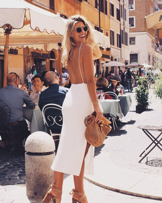 a white minimalist midi dress with a side slit and a fully open back on straps for a modern feel