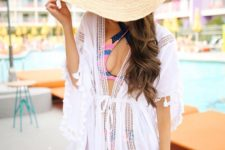 05 a colorful bikini with a criss cross top, a white mesh coverup, a large straw hat and a straw bag with colorful tassels
