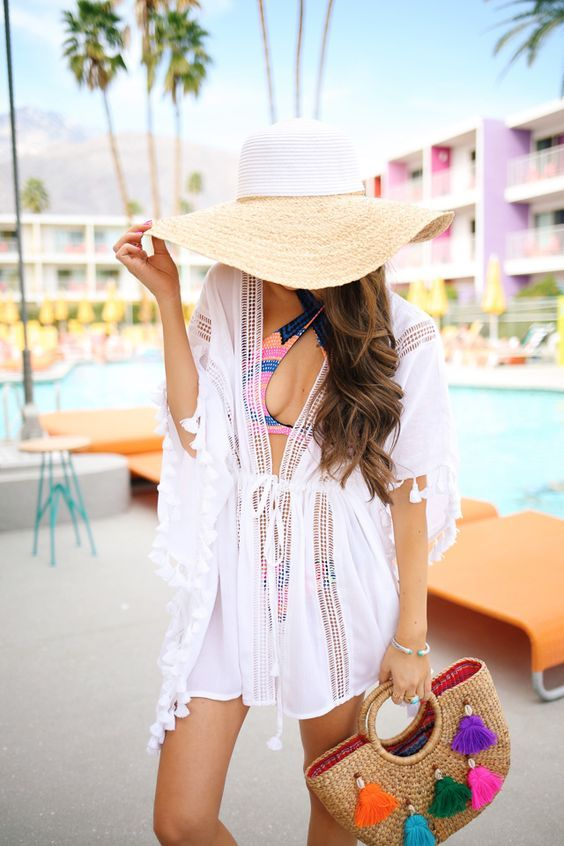 a colorful bikini with a criss cross top, a white mesh coverup, a large straw hat and a straw bag with colorful tassels