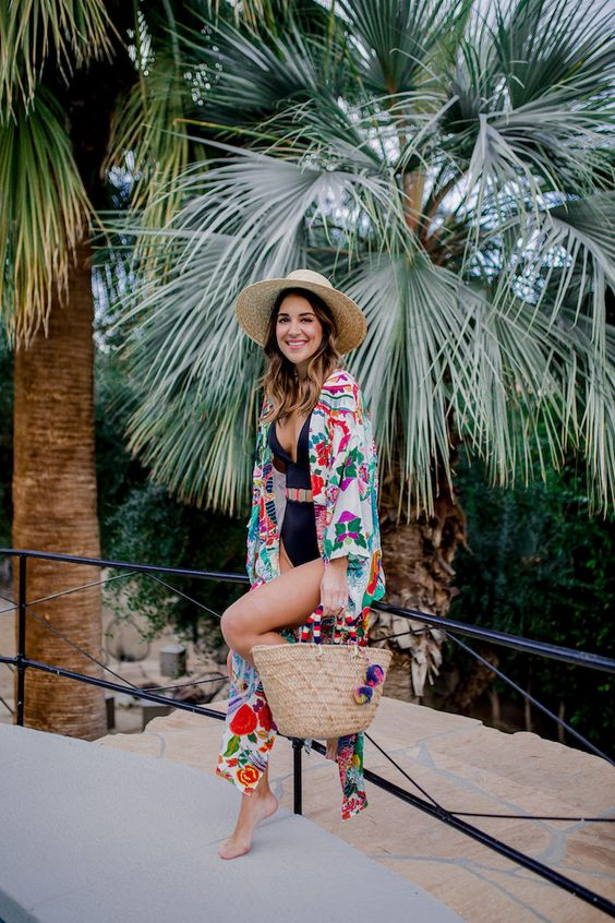 a colorful floral beach kimono paired with a black one piece make up a chic beach look with a right amount of print and color
