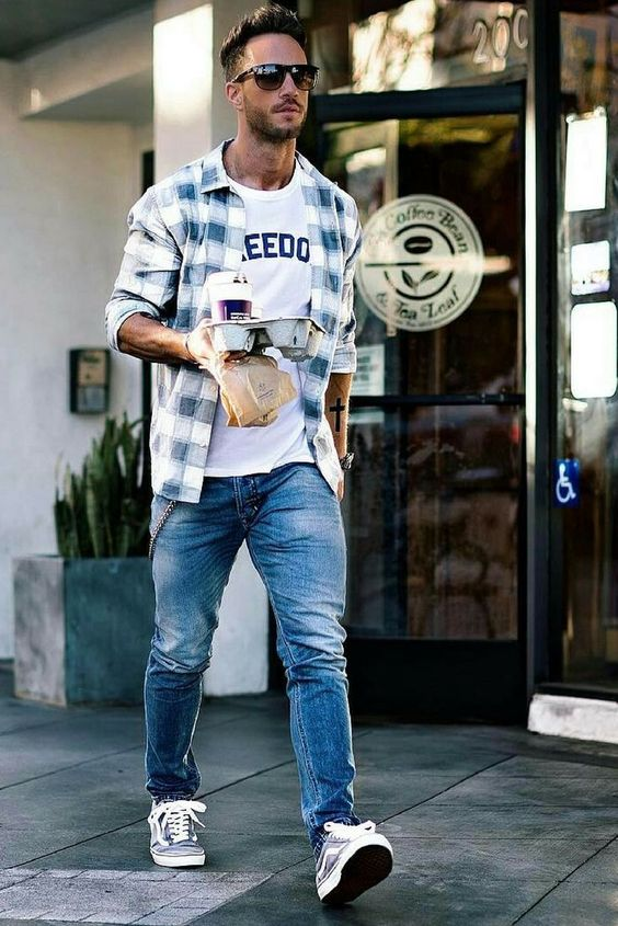 a printed tee, a checked shirt, blue jeans and grey sneakers for a casual and comfy look