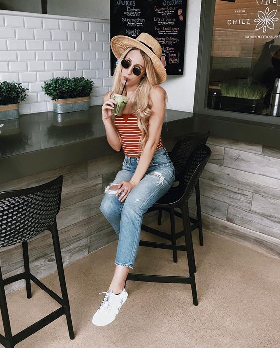blue ripped jeans, a striped red and white top, white canvas sneakers and a straw hat