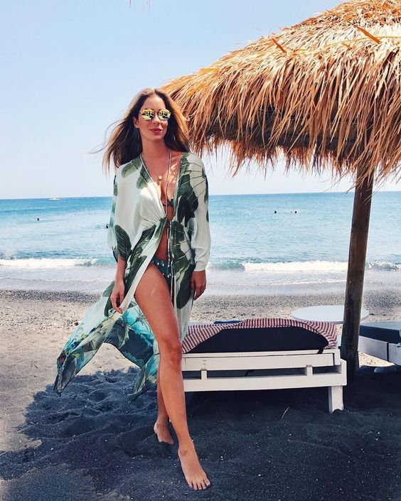 a green bikini with beads, a tropical print coverup, layered necklaces and gold sunglasses