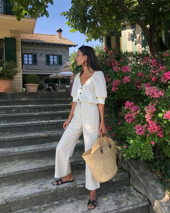 a holiday look with linen pants, a linen shirt on buttons, black slipper sandals and a straw bag