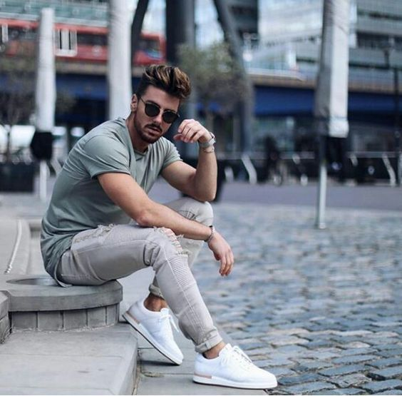 an olive green tee, grey ripped jeans and white sneakers for a casual and relaxed outfit