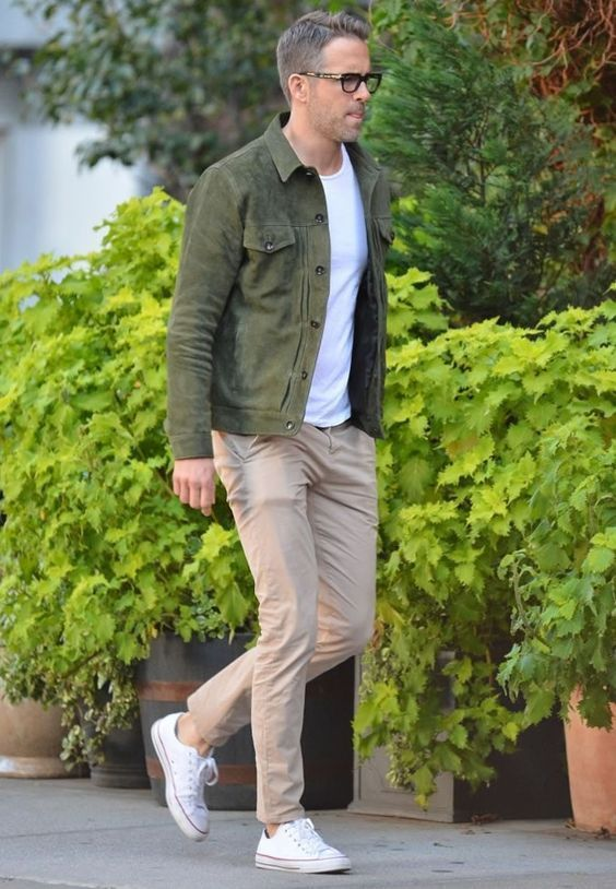 Ryan Reynolds rocking tan chinos, a white tee, a green jacket, white sneakers for a cool summer day