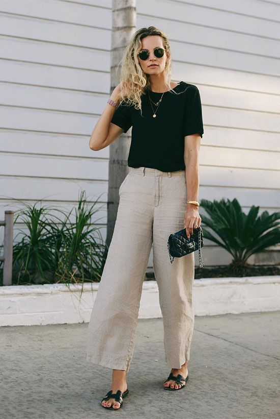a black basic t shirt, linen pants, black slipper sandals, a small black bag
