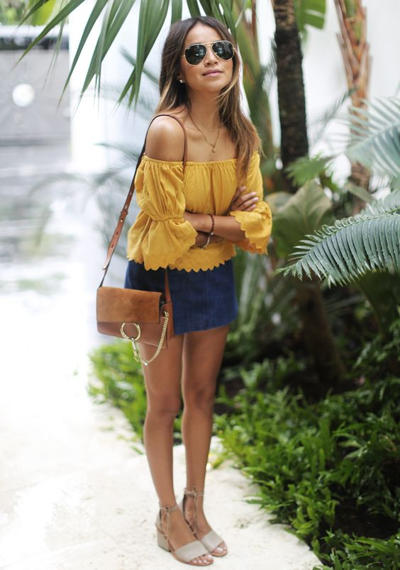 a bold look with an off the shoulder mustard top with long sleeves, a navy mini, neutral sandals and a brown bag