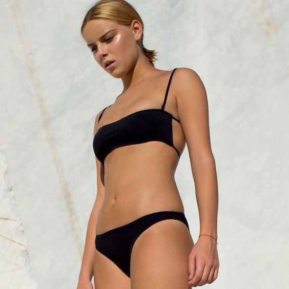 a minimalist black bikini with a laconic top that shows off a cool design with laces and a simple bottom