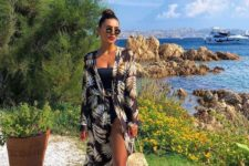08 a strapless black one piece swimsuit, a dark floral coverup, a straw round bag and a red lip