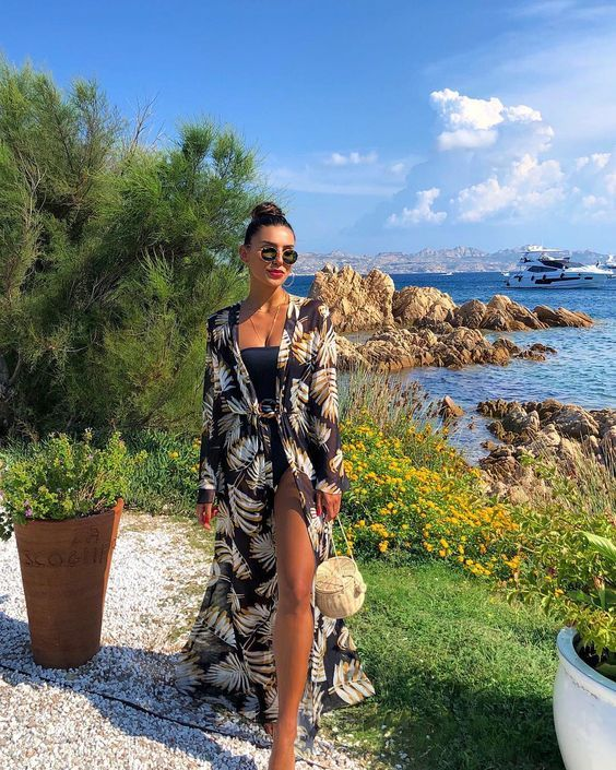 a strapless black one piece swimsuit, a dark floral coverup, a straw round bag and a red lip