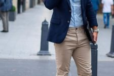 09 a casual work outfit with a blue button up, a navy jacket, tan chinos, white sneakers and a bracelet