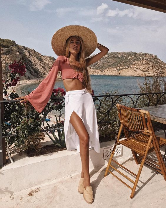 a dusty pink crop top with long bell sleeves, a white midi skirt with a slit, mules and a large straw hat