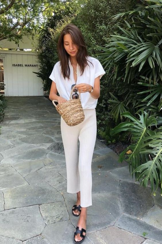 neutral striped pants, a white linen shirt, black slipper sandals and a little straw bucket bag