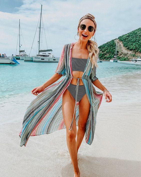 a colorful vertical stripe beach kimono and a a striped modern bikini make up a bold and fun look
