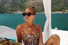 10 a leopard print one piece swimsuit withh statement earrings and a straw bag for a bit of edge