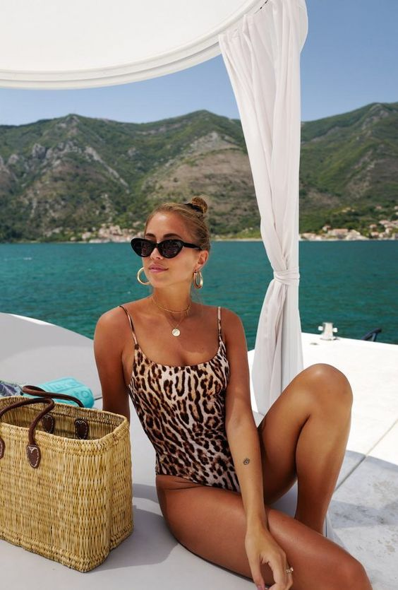a leopard print one piece swimsuit withh statement earrings and a straw bag for a bit of edge