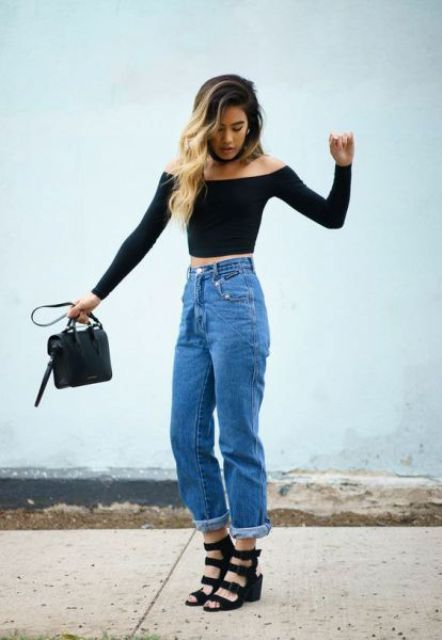 a party look with a black off the shoulder crop top, blue jeans, black strappy shoes and a black bag