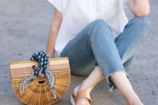 10 a white short sleeve linen shirt, blue jeans with fringe, tan slippers and a wooden bag