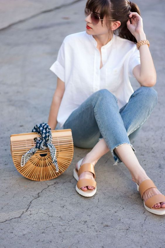 a white short sleeve linen shirt, blue jeans with fringe, tan slippers and a wooden bag