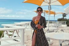 10 an orange one shoulder swimsuit with a black striped wrap dress over it, sandals and sunglasses