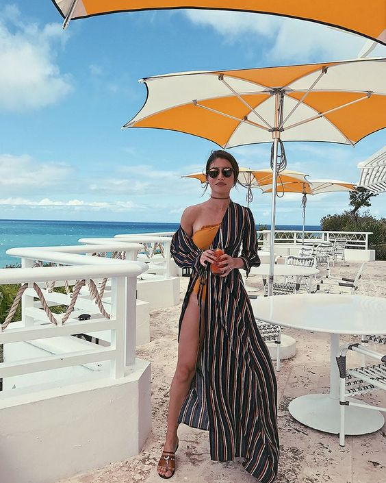 an orange one shoulder swimsuit with a black striped wrap dress over it, sandals and sunglasses