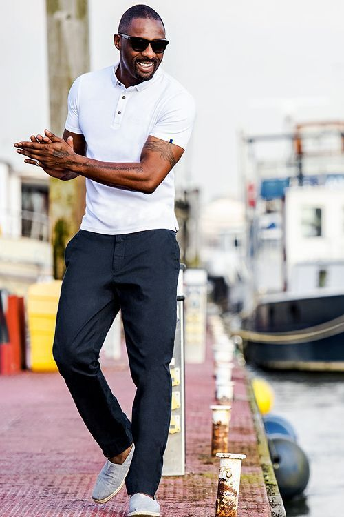 Idris Elba rocking a white polo shirt, navy pants and light blue espadrilles looks wow