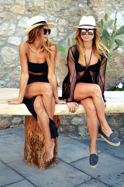 a black cutout one peice swimsuit with a black sheer coverup, denim espadrilles and a hat