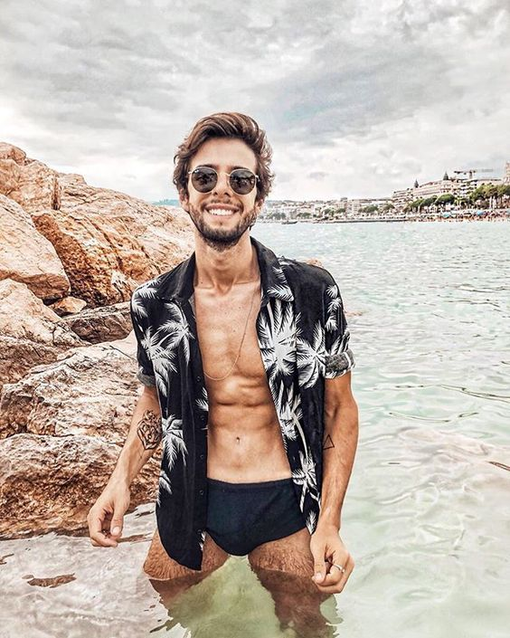 a black palm print shirt   a fresh take a classical bright piece, black trunks and sunglasses make up a monochromatic outfit