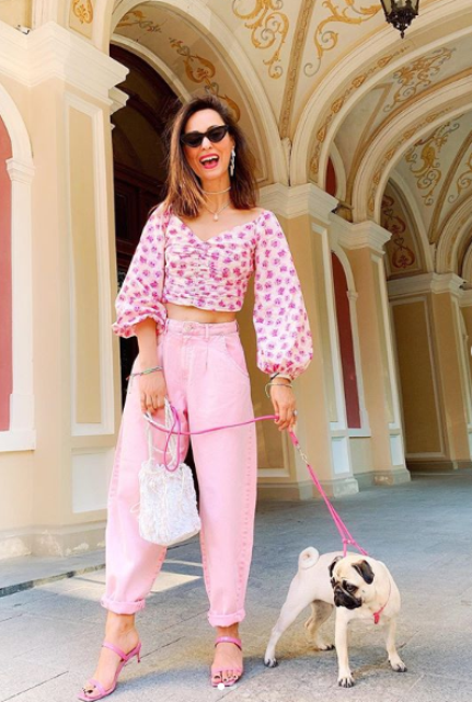 a pink floral print crop top with bell sleeves, pink cropped jeans and pink mules plus a white crochet bag