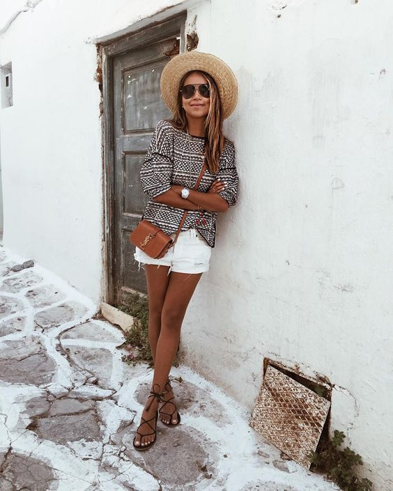 a printed top with short sleeves, white denim shorts with fringe, lace up sandals and a straw hat