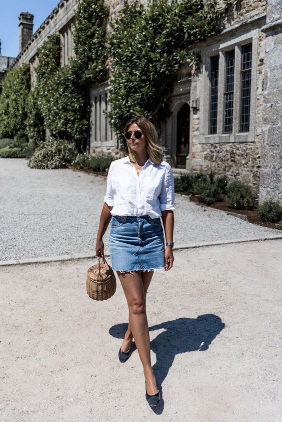 a white linen shirt, a blue denim skirt with a stepped hem, black shoes and a wicker bucket bag