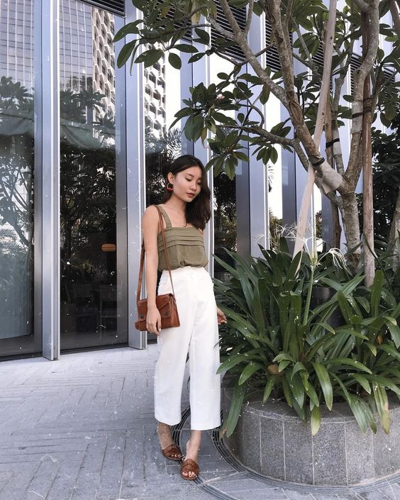 an olive green top on straps, white cropped pants, brown slipper sandals and a matching bag