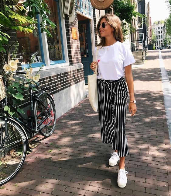 a comfy look with a white tee, black and white striped cropped pants, white sneakers and a tote