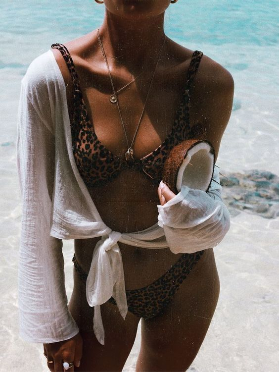 a minimal leopard print bikini with thick straps, layered necklaces and a tied shirt