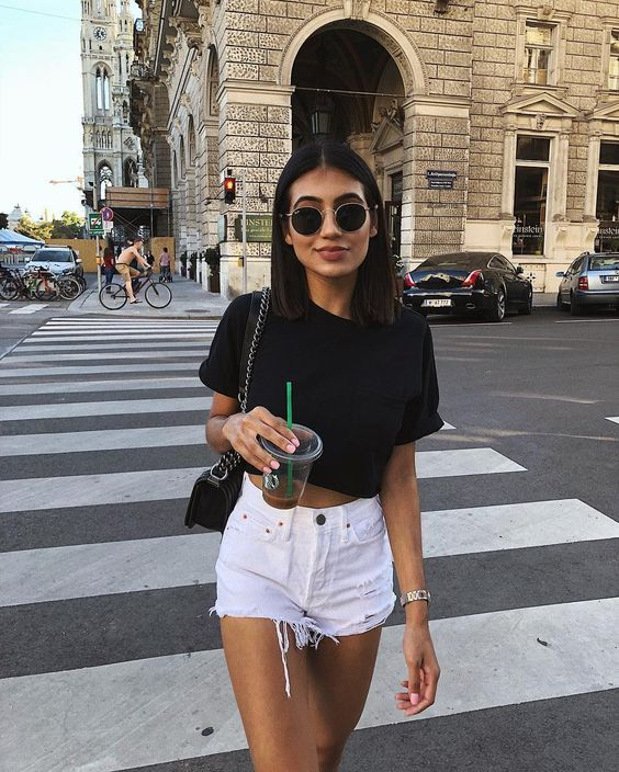 a sexy look with a black cropped tee, white denim shorts with fringe and a small bag