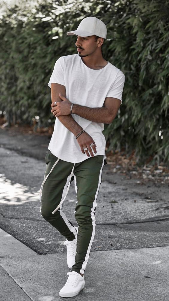 a sporty summer look with a white tee, a cap, green joggers and white sneakers