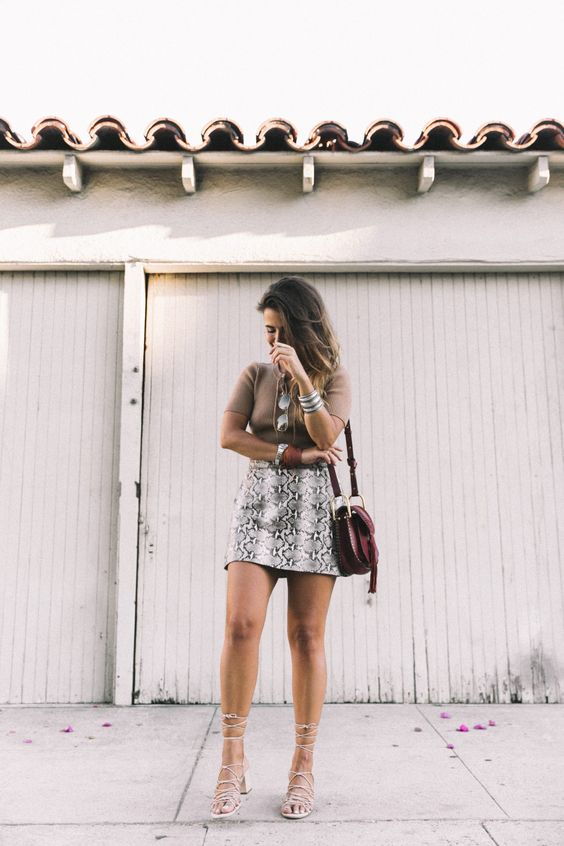 a camel top, a snake print mini skirt, lace up shoes and a brown saddle bag