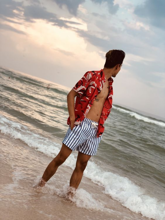 a red tropical print shirt and classic striped trunks make up a colorful and bright beach look