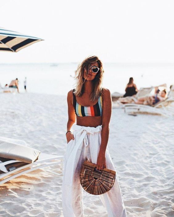 a sexy look with a croloful striped bikini top, white high waisted pants and a wooden bag