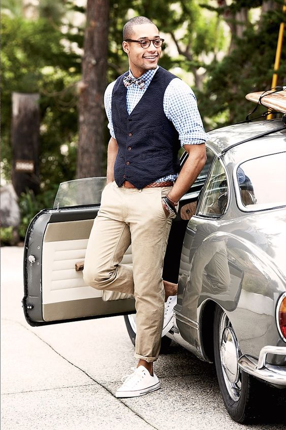 a casual yet chic work look with a plaid shirt, a navy waistcoat, tan pants, white sneakers and a plaid bow tie