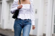 14 blue jeans, a white square neckline blouse with puff sleeves and a black bag
