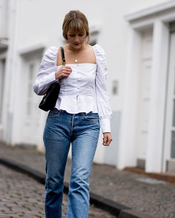 blue jeans, a white square neckline blouse with puff sleeves and a black bag