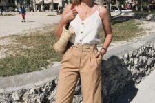 14 tan linen pants, a white top with buttons, brown slippers and a straw bag for a relaxed feel