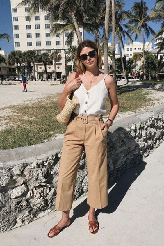 tan linen pants, a white top with buttons, brown slippers and a straw bag for a relaxed feel