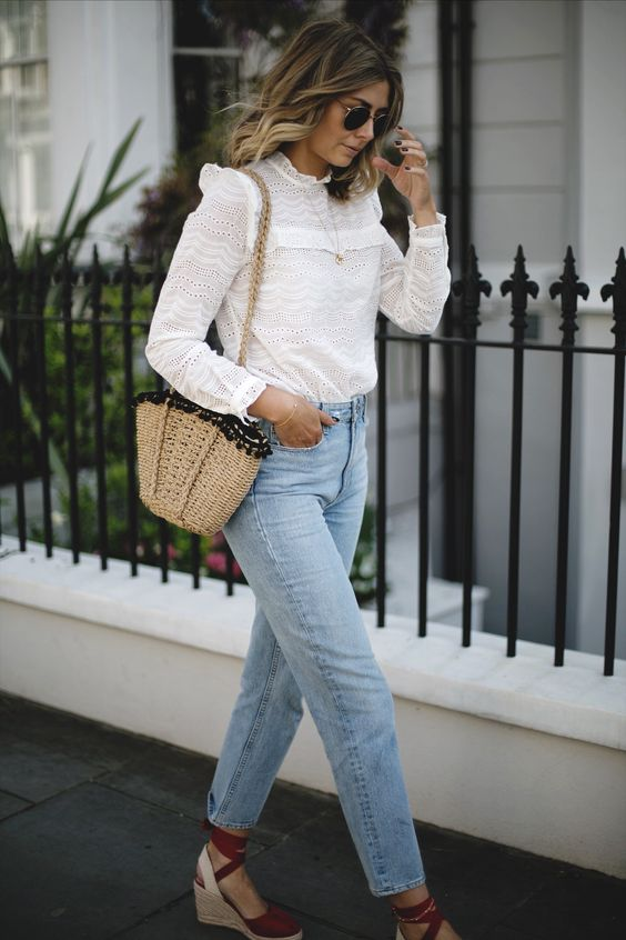 a white lace Victorian-style shir, bleached jeans, brown espadrilles, a straw bag with pompoms