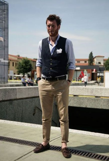 a smart casual look with a blue shirt, a navy waistcoat, tan pants, brown loafers and a handkerchief