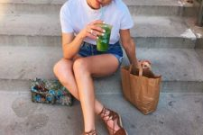 16 a white tee, blue denim shorts, rown espadrilles and a colorful bag with embellishments