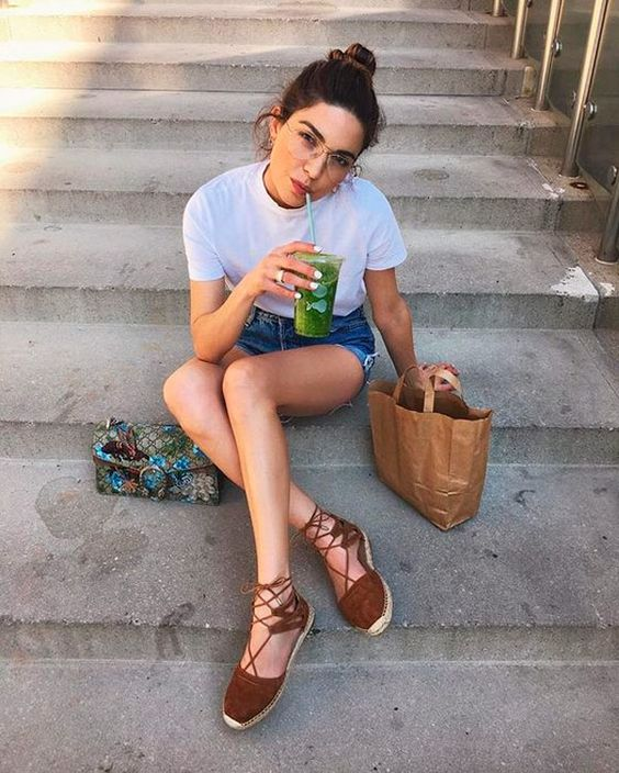 a white tee, blue denim shorts, rown espadrilles and a colorful bag with embellishments