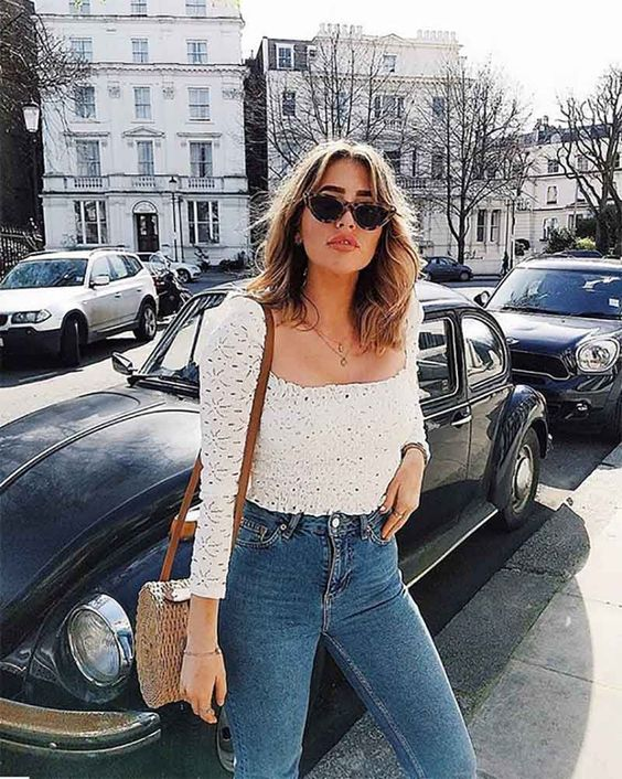 blue jeans, a white lacesquare neckline top with long sleeves and a wicker bag